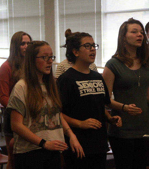 Lily Chidester, in the front row at the left, warms up with the Madrigals Choir.