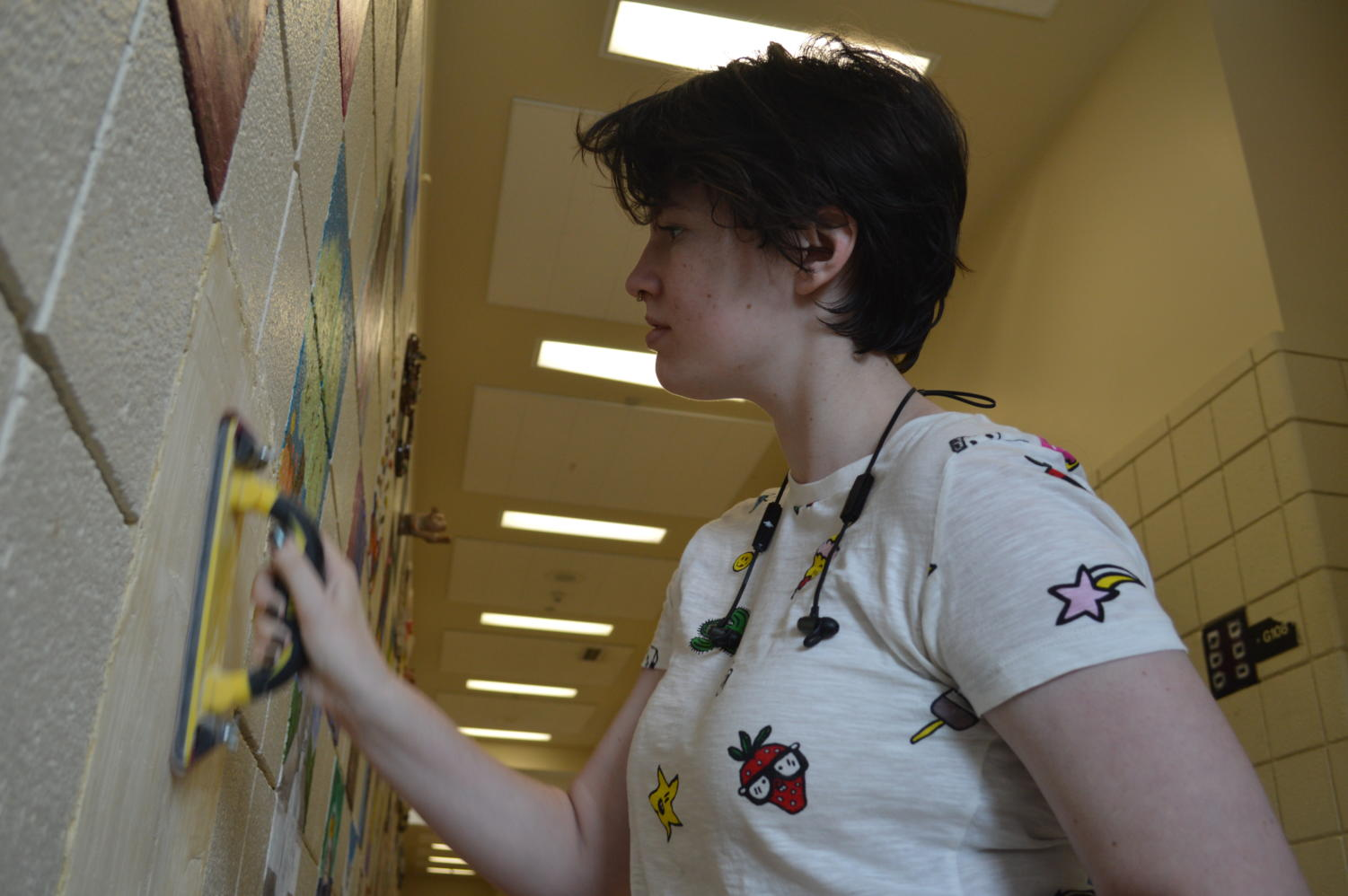 Miranda Roland prepares her spot on the art hall wall to paint.