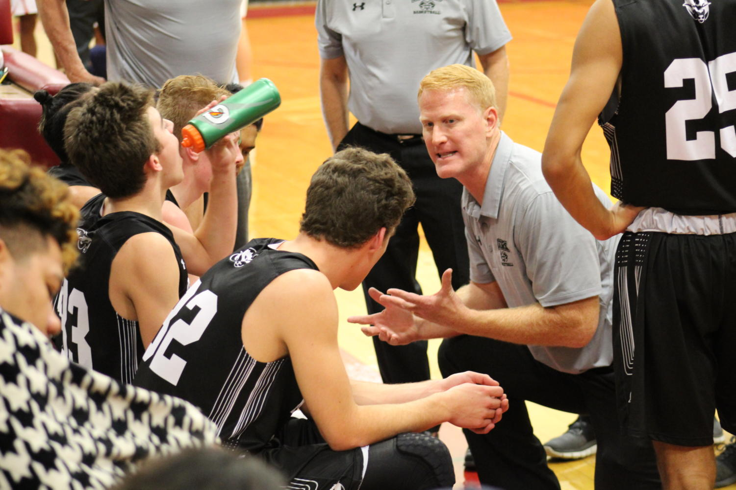 Head coach of the Rams, Jim Boyce, gives the players a pep talk during a timeout.