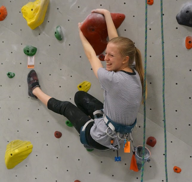 Brynley Anderson demonstrates an interesting climbing move to members of her club.