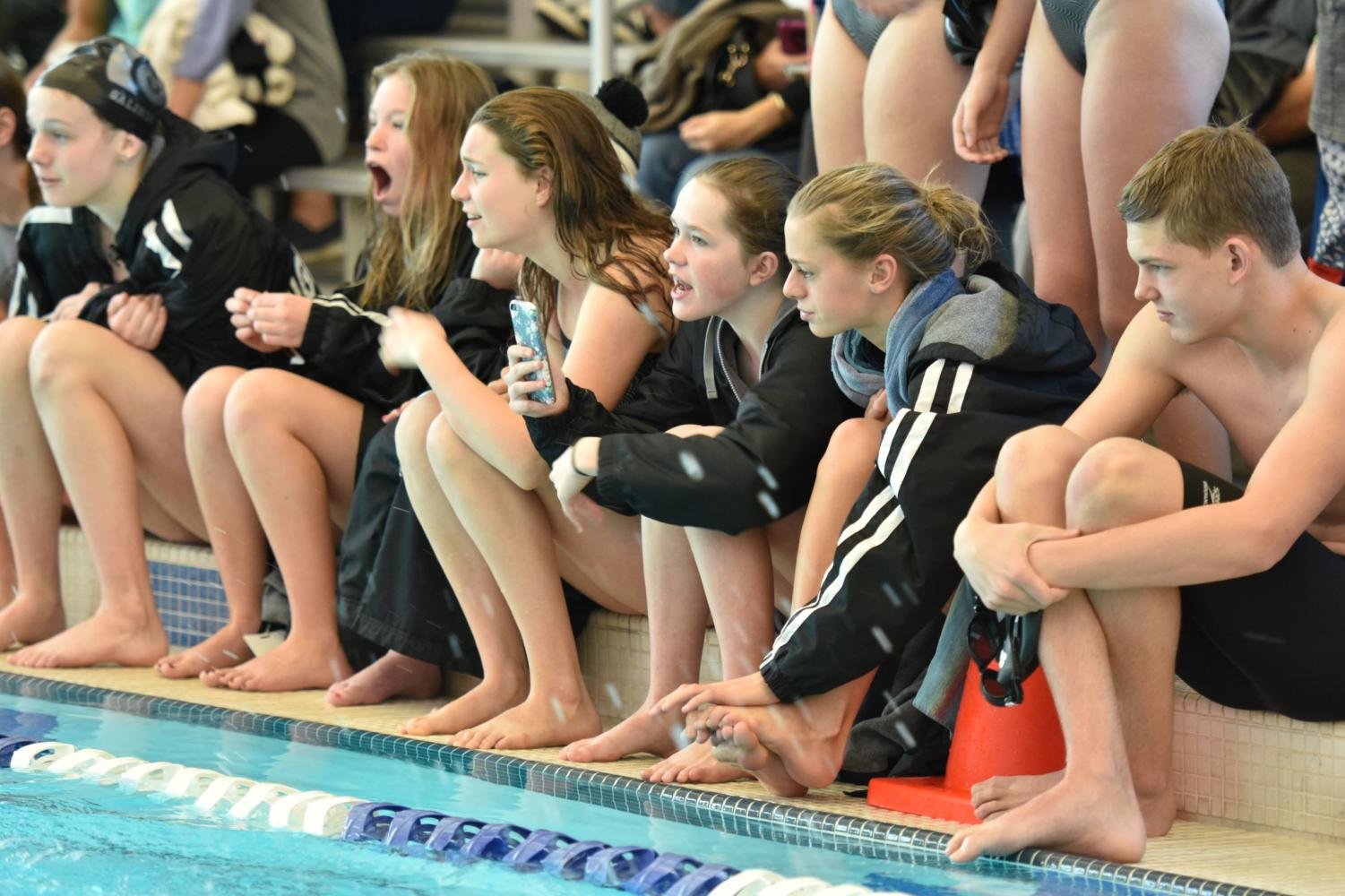 The Highland swimmers cheer for their teammates while they race.