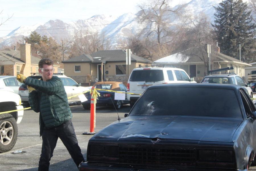 Highland student smashing car for softball fundraiser.