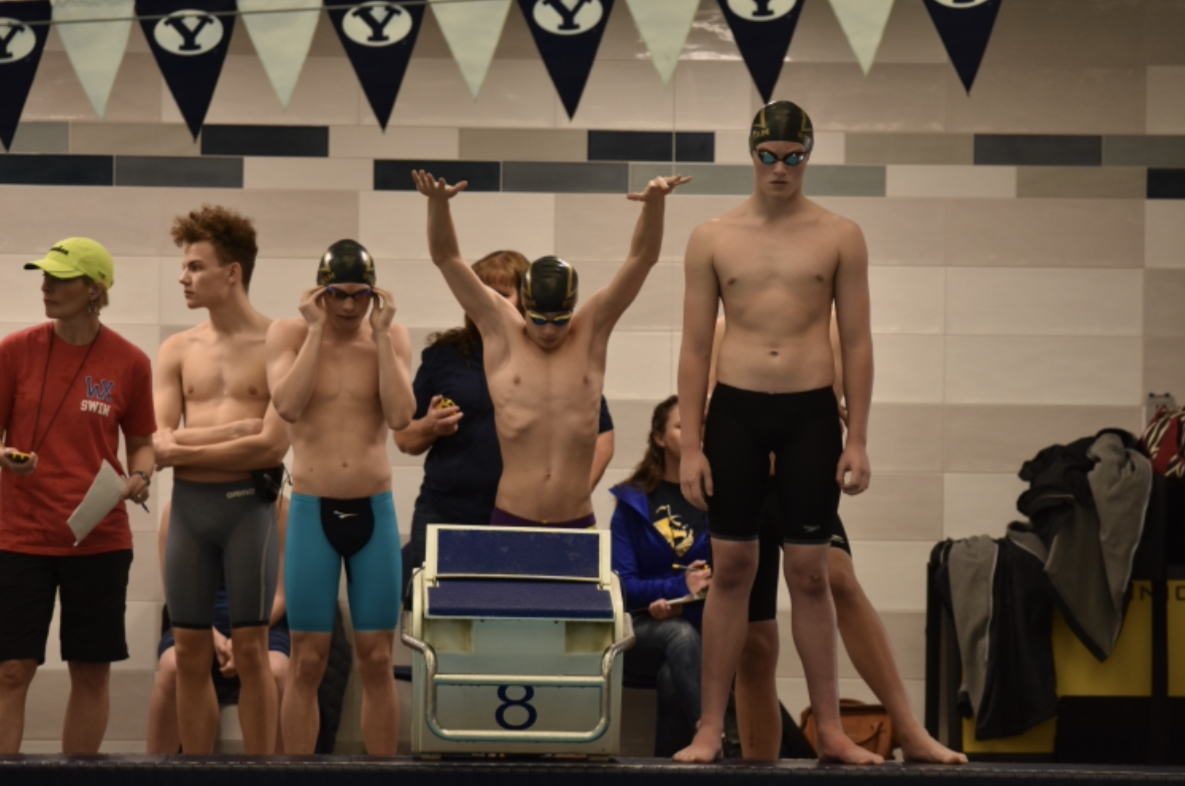 Members of Highland's men's 200 yard medley relay stand behind the block in preparation for their race.