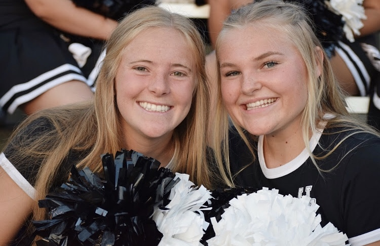 Pep Club members Tessa Croft (left) and Clara Larsen (right) help cheer on the Rams at a football game earlier this year.