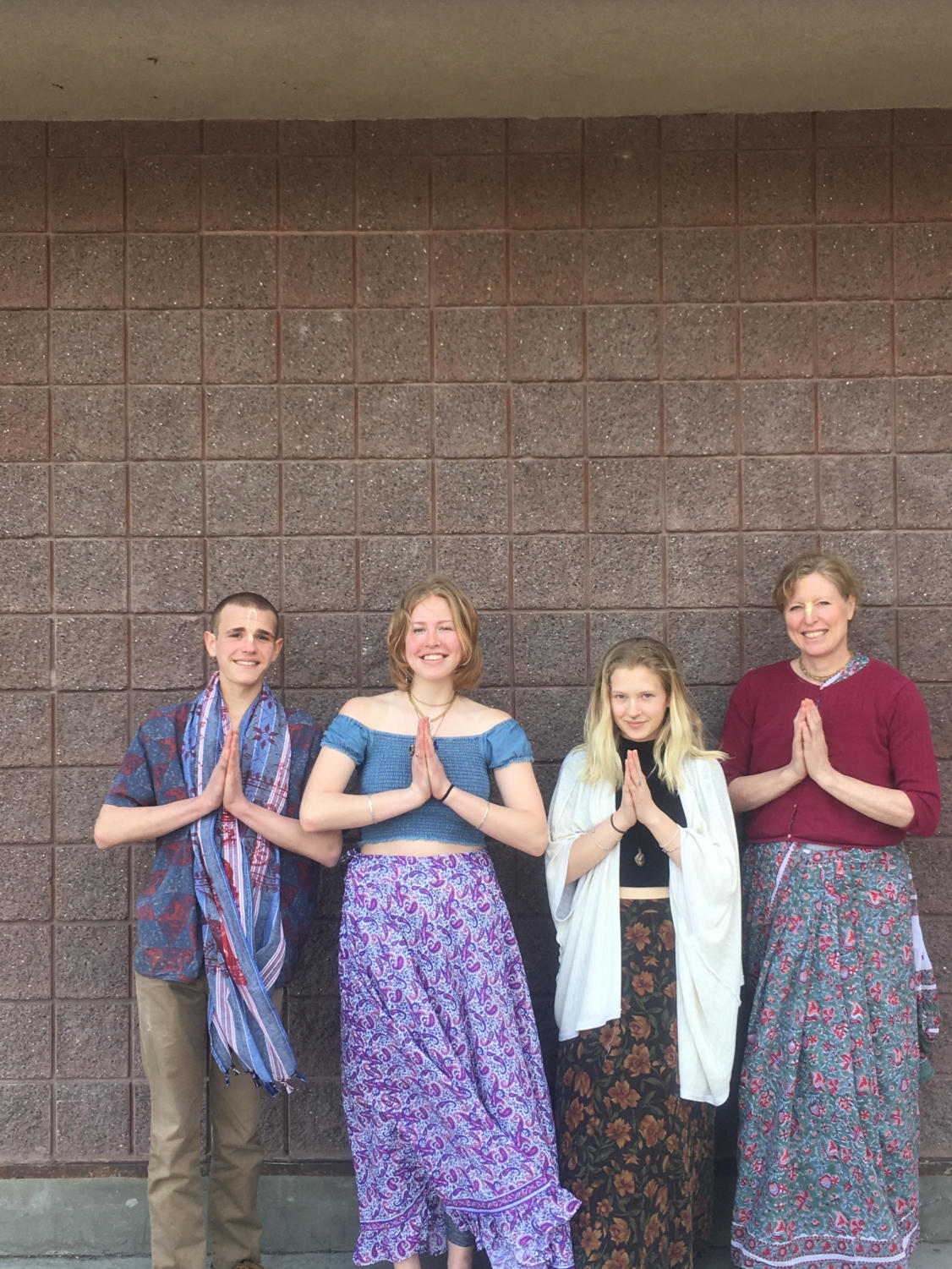 Shyamamohini Diana, pictured second, her mother, far right, and the two co-heads of the Bhakti Yoga club stand in front of the school in prayer pose.