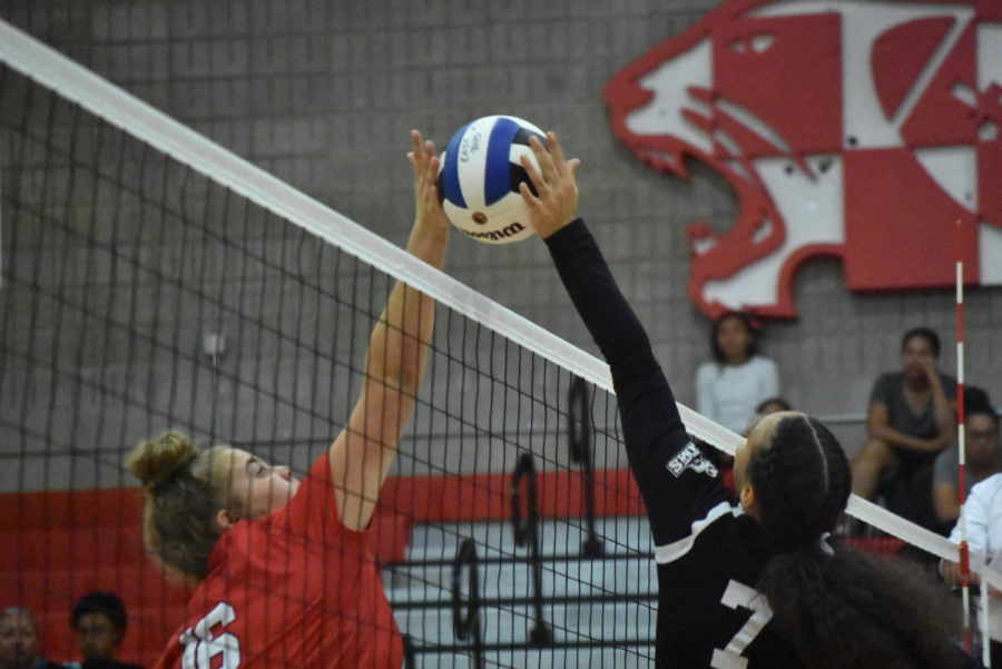 Players on both sides of the net jump for the ball.