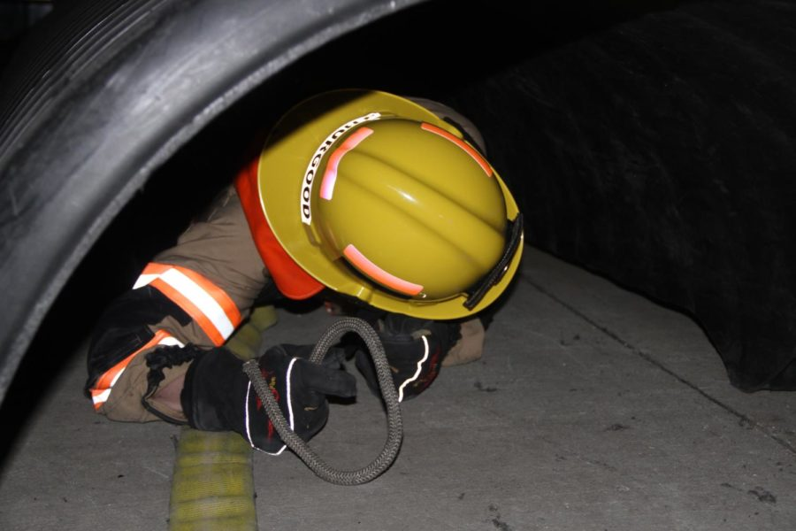 Charlie Goudelock crawls through a makeshift tunnel in a search and rescue drill.