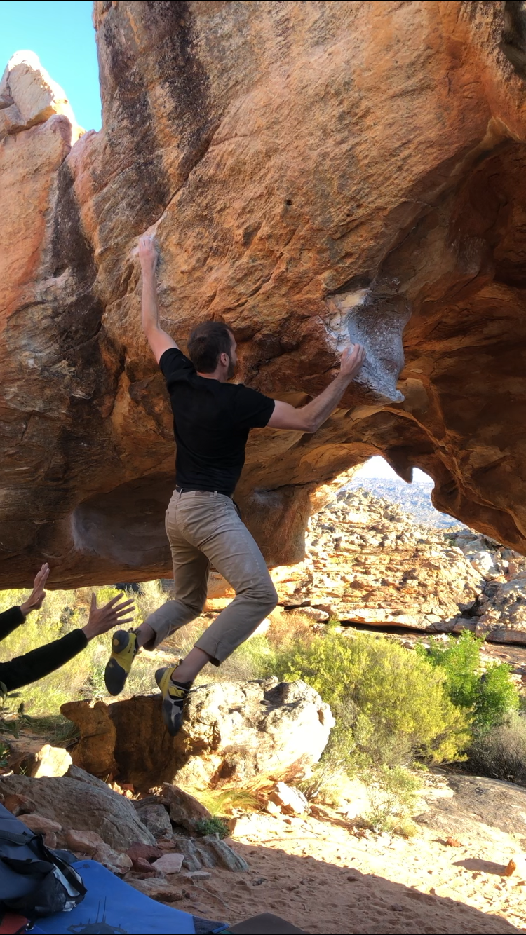 Creed Archibald hangs from a boulder problem in the Cederberg Mountain in South Africa.