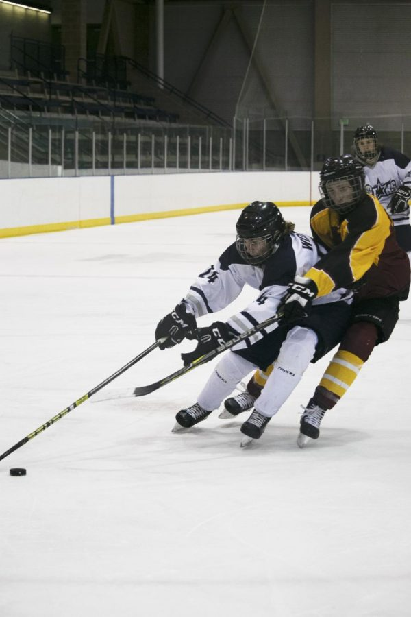 Highland fights for the puck in a UHSH hockey game.