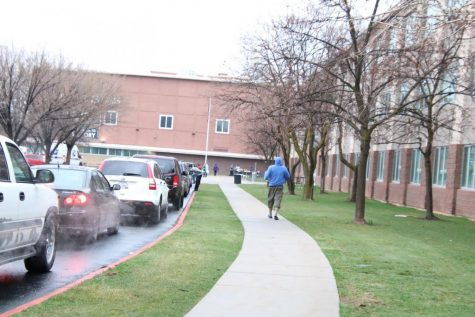 Cars line up outside Highland so that students can pick up laptops for home learning.