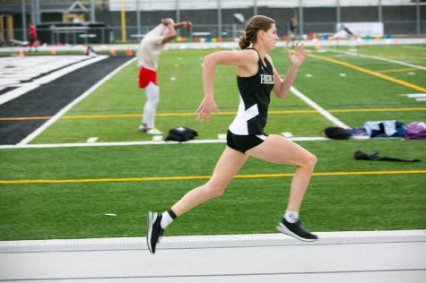 Annie Murdock running at a home meet.