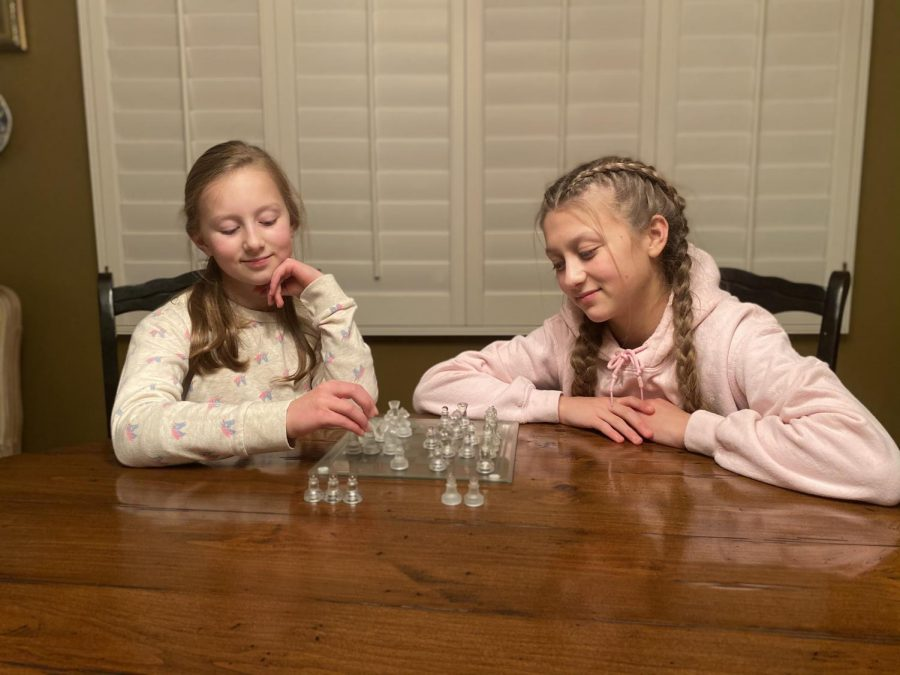 Two sisters play chess to bond and pass the time at home.
