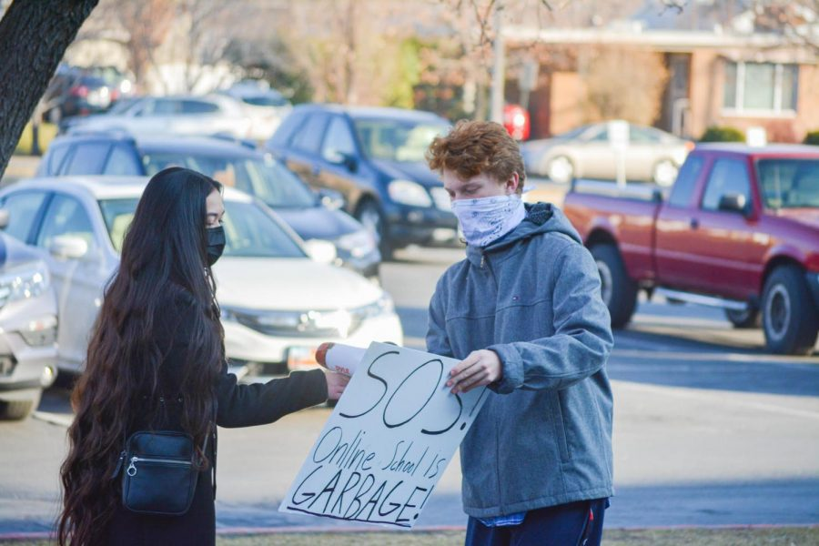Highland students Viviena Wolfgramm and Josh Richards rally in front of Highland on Monday, Dec. 7.