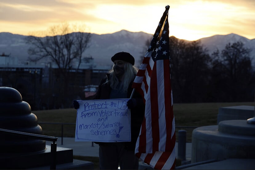 """Trump supporter holds sign about voter fraud and """"Marxist/Satanist"""" schemes"""