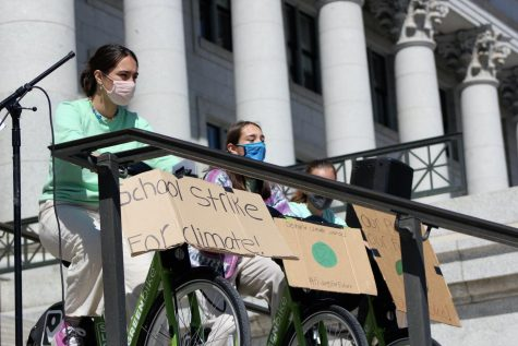 Students pedal bikes to power speakers at the Earth Day protest.